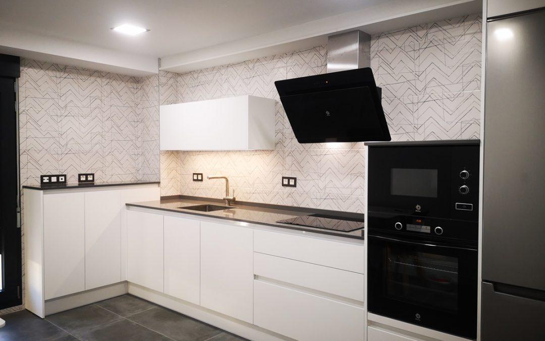 Cocina moderna blanca con electrodomésticos negros